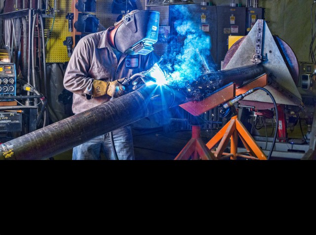 Team Industry welder using a welding positioner to fabricate a pipe spool.